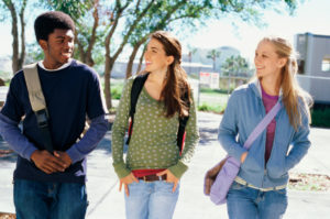 Three teenagers walking and smiling